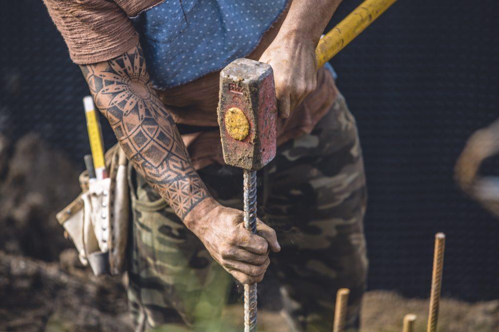 operaio edile al lavoro in cantiere con martello